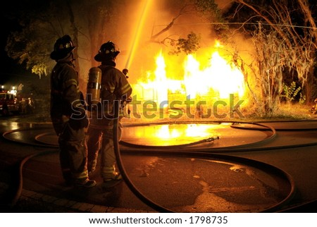 Firefighters suppress blazing fire - stock photo