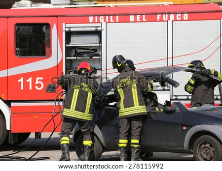 Firefighters take off the hood of the car after a serious car accident - stock photo