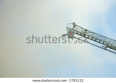 Firefighters' tools,  hose and ladder in action on a burning building in Quebec country, Canada - stock photo