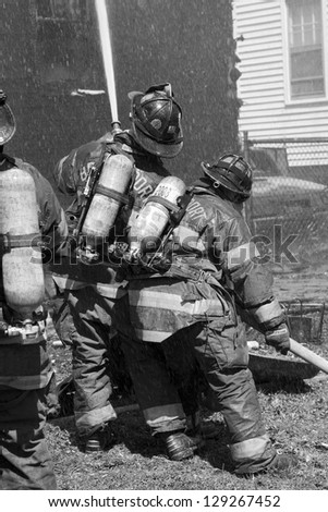 Firefighters work together to battle a house fire. - stock photo