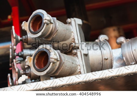 Firefighting equipment on red fire truck. Water hydrants close-up photo with selective focus - stock photo