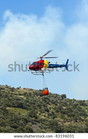 Firefighting helicopter carrying water to extinguish the fire - stock photo