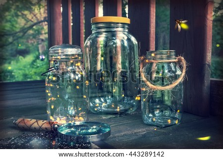 Fireflies in jars in a tree house, with magnifying glass. Long exposure, focus on top of jar on the left - stock photo