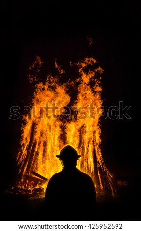Fireman at night fighting a raging fire with huge flames of burning timber - stock photo