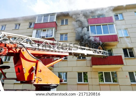 fireman climbing a ladder with water hose for extinguish fire - stock photo