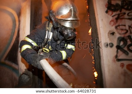 Fireman extinguishing fire inside an old house in Prague. - stock photo