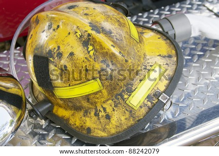 fireman helmet on fire truck bumper - stock photo