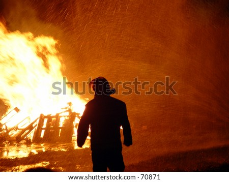 Fireman in front of a fire with water spray visible