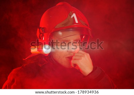 Fireman in smoke using walkie-talkie and looking away. Head and shoulders studio shot isolated on white. - stock photo