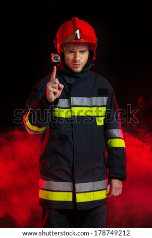 Fireman's safety notice. Firefighter in red helmet standing in smoke and pointing. Three quarter length studio shot on black background.