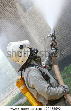 Fireman spraying water in a smouldering burnt out house - stock photo