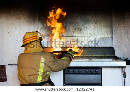 Fireman trying to put an oil fire out with a chopping board - stock photo