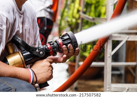 Fireman using water hose to prevent fire - stock photo