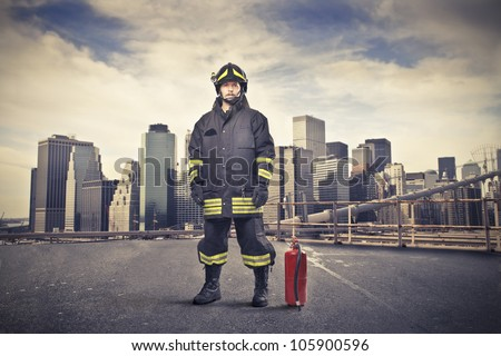 Fireman wearing his uniform with a fire extinguisher beside him and cityscape in the background - stock photo