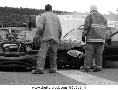 Firemen and ambulances at the scene of a serious car accident on a dark rainy fall day, desaturated.  Part of a series. - stock photo