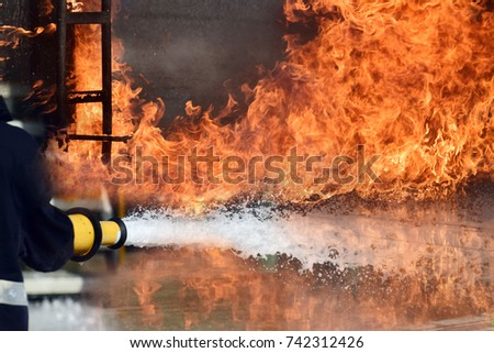 Firemen ,Fireman in action activated foam . ,Background for emergency  response .
