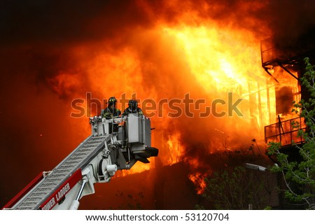 Firemen on a crane against wall of fire - stock photo