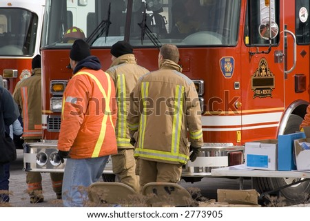 firemen on background of firetruck - stock photo