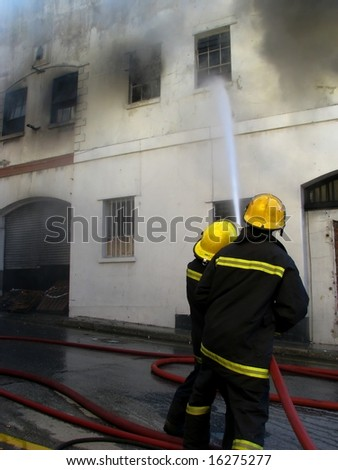 Firemen putting out fire in old building - stock photo