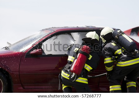 firemen with a burning car - stock photo