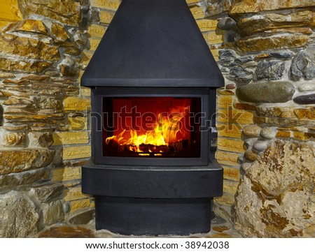 fireplace and fire with stone walls - stock photo