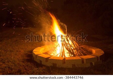Fireplace at night on a dark background with flames and sparks.