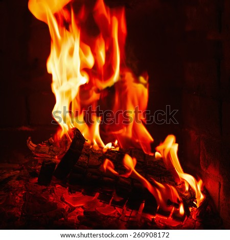 Fireplace burning. Warm burning and glowing fire in fireplace. Close up. Cozy background. - stock photo