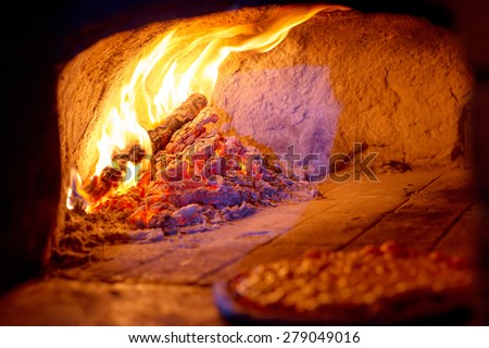 Fireplace burning. Warm burning and glowing fire in traditional brick oven for baked pizza - stock photo