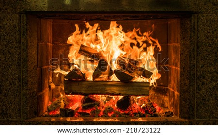 Fireplace burning. Warm cozy burning fire in a brick fireplace close up. Cozy background.  - stock photo