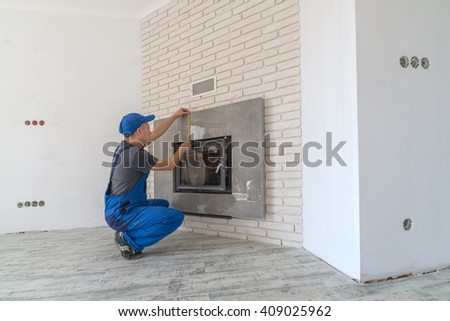 Fireplace installing in white brick wall - stock photo
