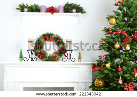 Fireplace with beautiful Christmas decorations in room - stock photo