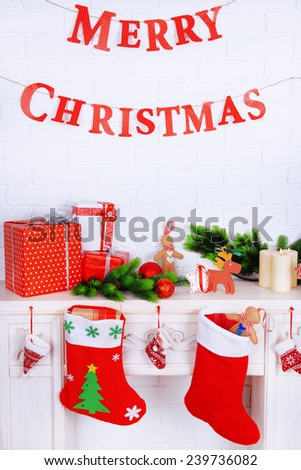 "Fireplace with Christmas decoration and inscription ""Merry Christmas"" on brick wall background"