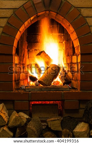 firewood and fire in fireplace in country cottage