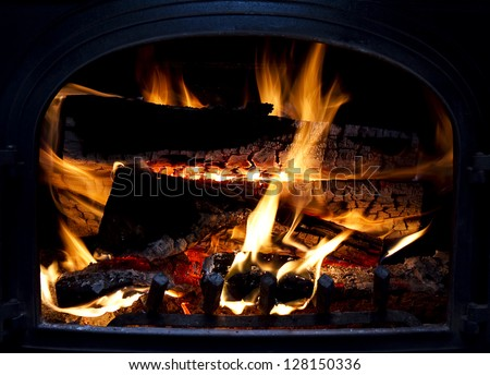 Firewood burning inside  arch wood-burning stove - stock photo