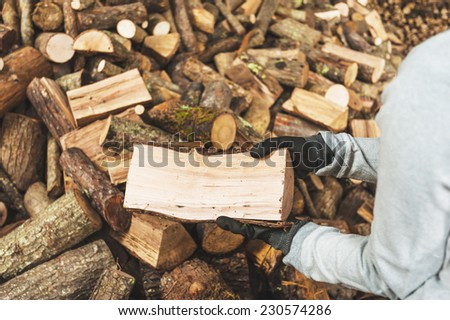 Firewood in a piece of wood stored on the stack, hands holding a piece of firewood - stock photo