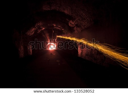 firework set off inside a dark tunnel at night exploding in the distance - stock photo