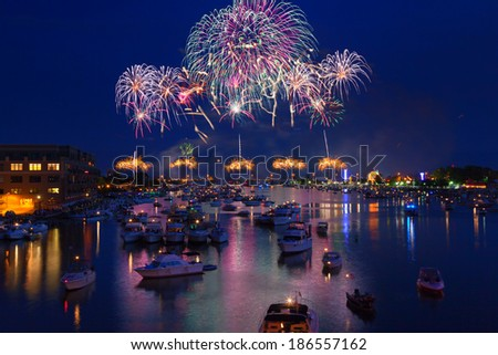 Fireworks explode in a glorious display over the Saginaw River at Bay City Michigan's annual fireworks show. Crowds gather in boats on the river to watch the display and celebrate Independence Day. - stock photo
