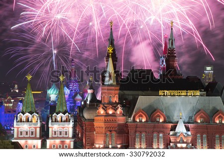 Fireworks explode over Kremlin, St. Basil Cathedral at night on Red Square in Moscow. Text on building: historic museum - stock photo