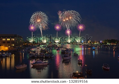 Fireworks explode over the Saginaw River during the 50th anniversary celebration on July fourth in Bay City Michigan, 2012 - stock photo