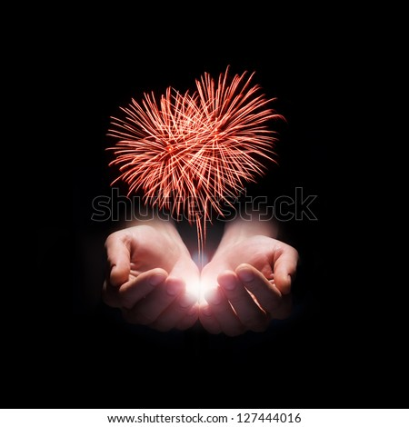 fireworks in the men's hands in the shape of a red heart on black background - stock photo
