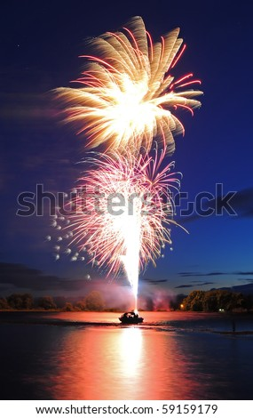 Fireworks launching from a boat floating on the river up into the sky. - stock photo
