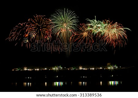 Fireworks light up to sky with dazzling display and reflect to river at new year  - stock photo