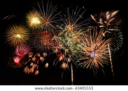 Fireworks of different colors against a dark sky - stock photo