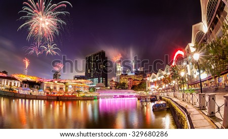 Fireworks set off in the backdrop to the Singapore River along Clarke Quay as a precursor to Singapore's 50 years of independence celebration. - stock photo