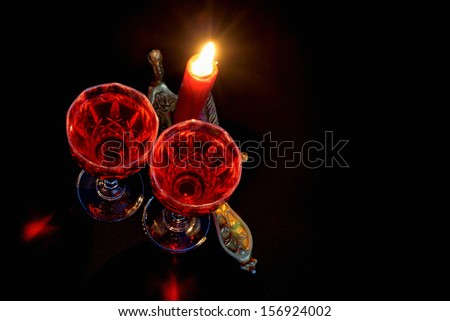 Firing red candle in vintage candlestick and two winglasses of red wine on dark background - stock photo