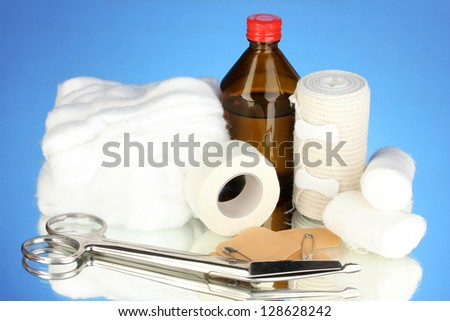 First aid kit for bandaging on blue background - stock photo