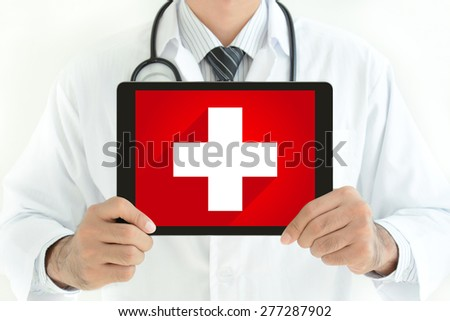 First aid sign on tablet pc screen held by doctor - stock photo