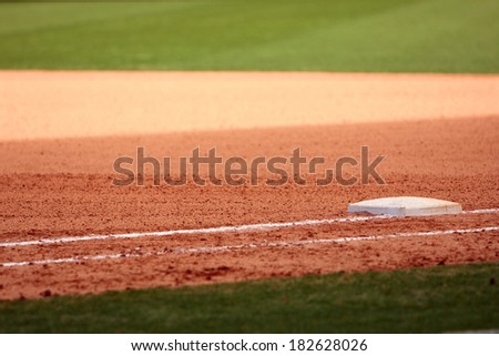 First base is featured in empty baseball field, showing infield dirt and outfield grass. - stock photo