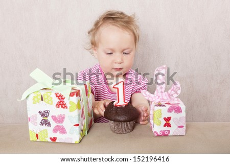 First birthday. Charming caucasian baby girl with presents and birthday cake on beige background.  - stock photo