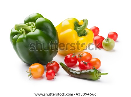 first crop of fresh vegetables bell peppers, cherry tomatoes and chili close-up isolated on white background